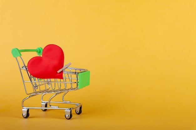 Großes rotes herz mit stift auf mini-einkaufswagen, einkaufs-, verkaufs- und liebeskonzept, valentinstag, gelbe wand, kopierraum, horizontal