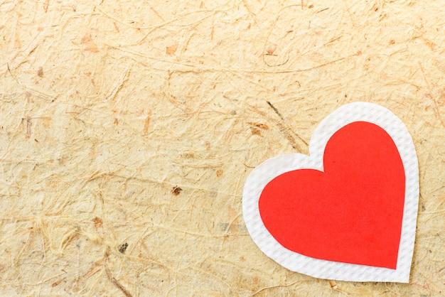 Großes rotes und weißes herzpapier auf hintergrund des braunen papiers. liebe und valentinsgrußkonzept.