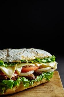 Großes sandwich auf schwarzem hintergrund holzbrett street food, fast food. hausgemachte burger mit rindfleisch, käse auf dem holztisch. getöntes bild.