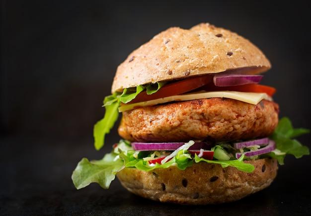 Großes sandwich - hamburger mit saftigem hühnchenburger, käse, tomate und roten zwiebeln auf schwarzem tisch