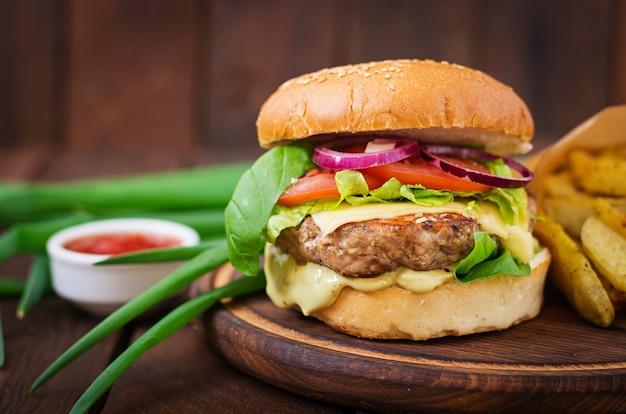 Großes sandwich - hamburger mit saftigem rindfleischburger, käse, tomate und roten zwiebeln auf holztisch