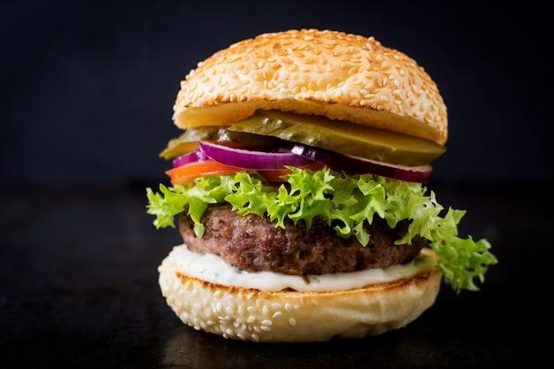 Großes sandwich - hamburgerburger mit rindfleisch, essiggurken, tomate und remoulade auf schwarzem hintergrund.