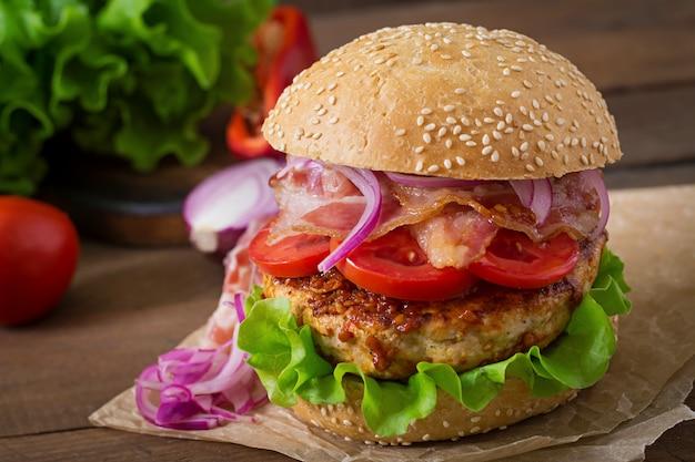 Großes sandwich - hamburgerburger mit rindfleisch, roter zwiebel, tomate und gebratenem speck.
