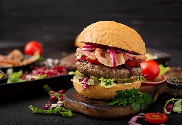 Großes sandwich - hamburgerburger mit rindfleisch, tomate, in essig eingelegter gurke und gebratenem speck.