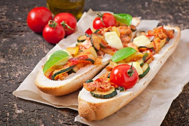 Großes sandwich mit gebratenem gemüse mit käse und basilikum auf alter holzoberfläche