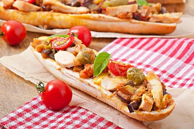 Großes sandwich mit gebratenem gemüse und huhn mit käse und basilikum auf alter holzoberfläche