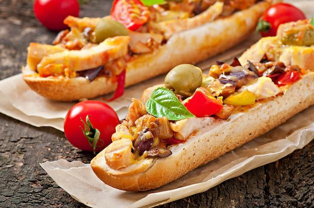 Großes sandwich mit gebratenem gemüse (zucchini, aubergine, tomaten) und huhn mit käse und basilikum auf alter holzoberfläche