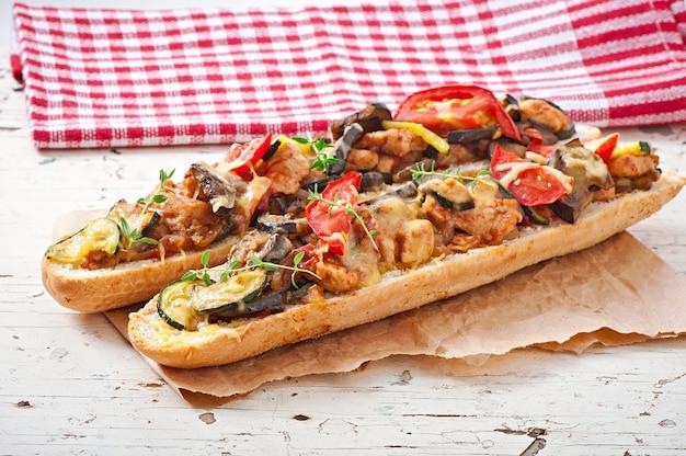 Großes sandwich mit geröstetem gemüse (zucchini, auberginen, tomaten) mit käse und thymian auf altem holzhintergrund