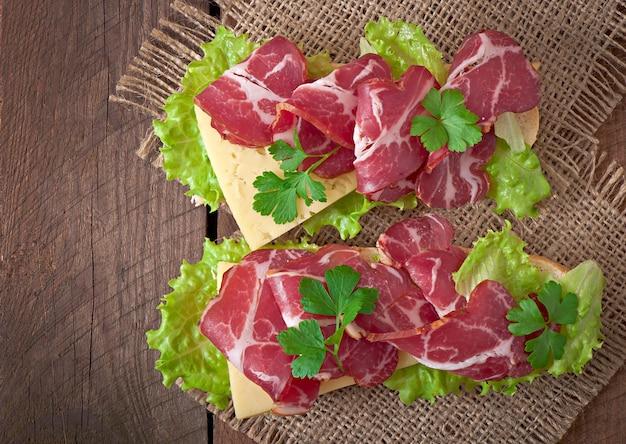 Großes sandwich mit rohem geräuchertem fleisch auf einer holzoberfläche