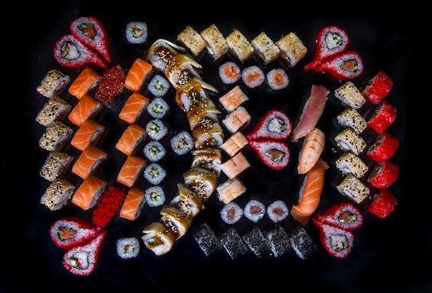 Großes set sushi und brötchen der japanischen küche draufsicht auf schwarz