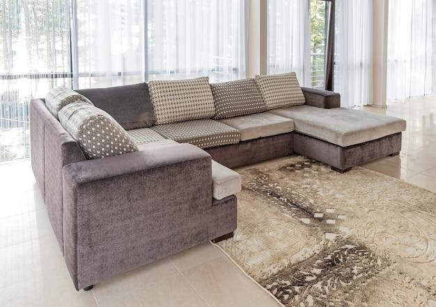 Großes sofa und eine große fenstereinrichtung mit morgensonne aus den fenstern