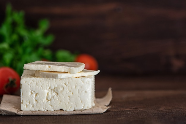Großes stück feta-käse auf dunklem holztisch. selektiver fokus Premium Fotos