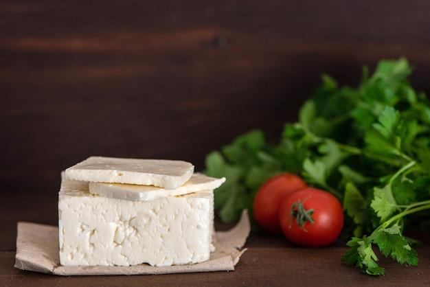 Großes stück feta-käse auf dunklem holztisch.