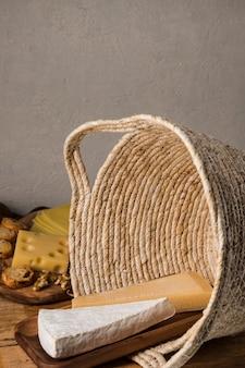 Großes stück käse auf hölzernem behälter im weidenkorb