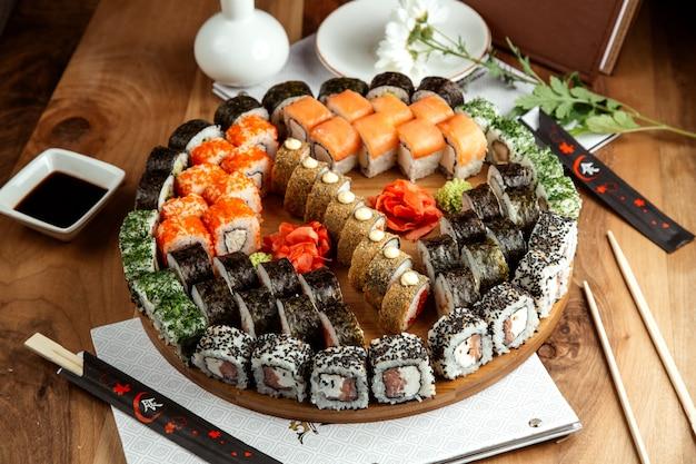 Großes sushi-set philadelphicalifornimidori makki und heiße brötchen an bord an bord