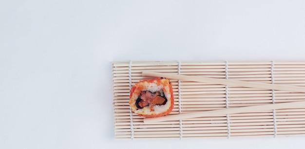 Großes sushi und stäbchen isoliert auf einem licht