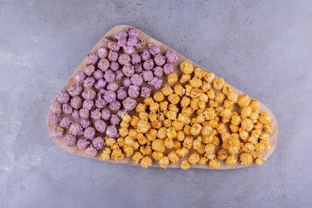 Großes tablett mit verschiedenen aromen von popcorn-süßigkeiten, die auf marmorhintergrund gehäuft sind. foto in hoher qualität