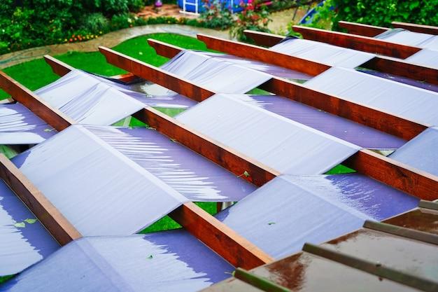 Großes terrassendach mit stoffpaneelen und holzbalken zum sonnenschutz
