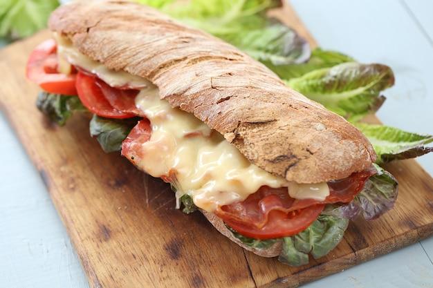 Großes veganes sandwich mit gemüse auf holzbretttisch