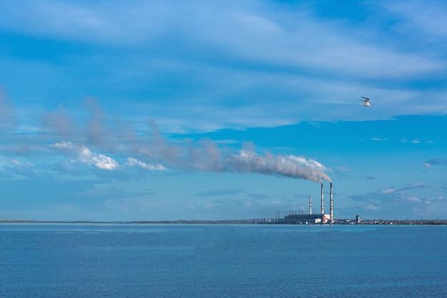 Großes wärmekraftwerk vor dem hintergrund eines großen blauen himmels und stausees