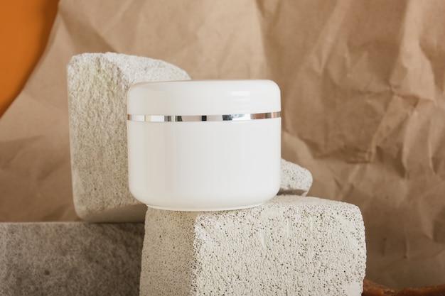 Großes weißes plastikgefäß für hautpflegekosmetik auf einem steinpodest auf einem braunen hintergrundkopierraum