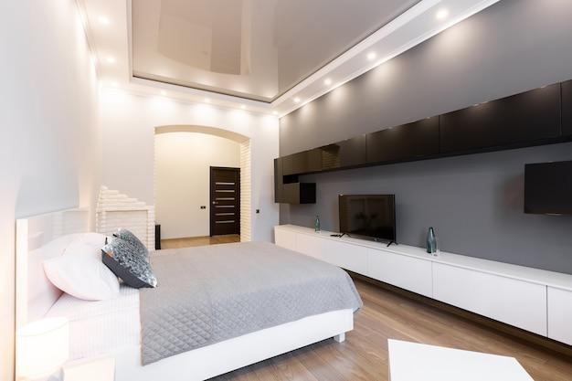 Großes wohnzimmer mit bett, möbeln und fernseher im modernen stil