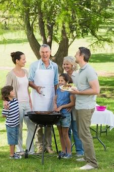 Großfamilie, die am grill im park steht