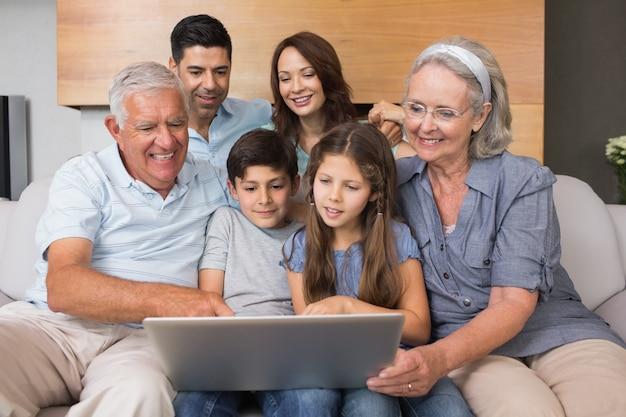 Großfamilie, die laptop auf sofa im wohnzimmer verwendet