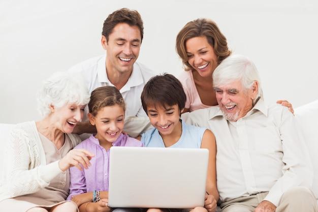 Großfamilie, die laptop betrachtet