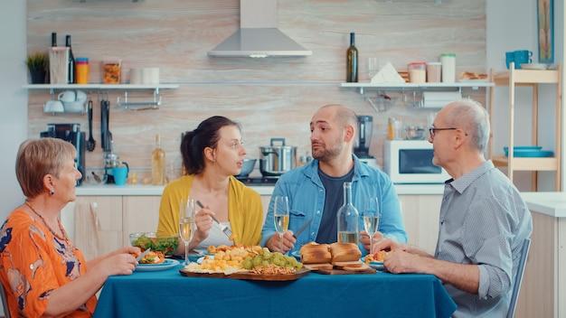Großfamilie spricht mit entspannender zeit. multi-generationen genießen die zeit zu hause, in der küche am tisch sitzen, gemeinsam zu abend essen und trinken
