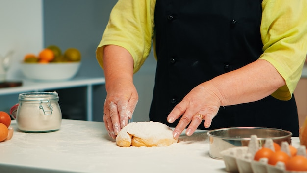 Großmutter bereitet hausgemachte donuts mit küchenschürze zu. seniorchef im ruhestand mit knochen und gleichmäßigem besprühen, sieben von weizenmehl mit handgebackener hausgemachter pizza und brot.