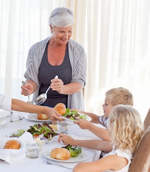 Großmutter, die anderen familienmitgliedern etwas zu essen während der mahlzeit gibt