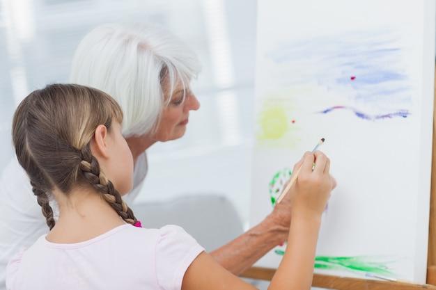 Großmutter, die enkelin beibringt, wie man malt