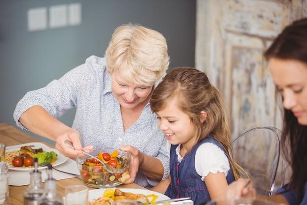 Großmutter, die enkelin beim frühstücken dient