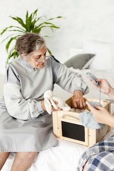 Großmutter, die zu hause altes spielzeug betrachtet
