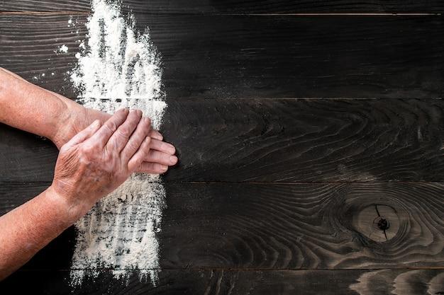 Großmutter hände einer alten frau mit mehl in der form eines herzens mit mehl auf dunklem schwarzem tisch, lebensmittelrezeptmenühintergrund. platz für text. langes bannerformat