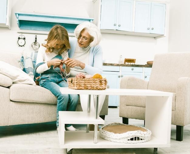 Großmutter hilft ihrer enkelin, während sie das stricken lernt