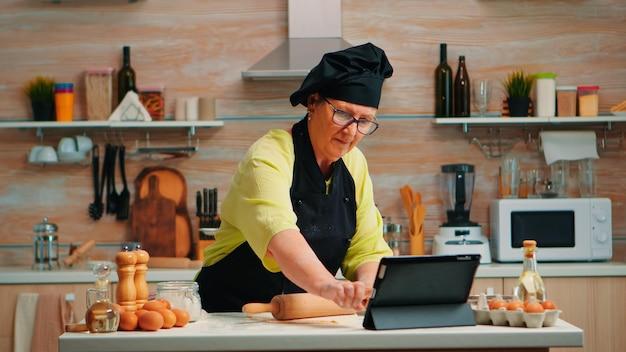 Großmutter hört videotipps für die zubereitung von hausgemachten kuchen. pensionierte dame, die einen kulinarischen podcast auf dem tablet verfolgt und ein koch-tutorial in den sozialen medien mit einem hölzernen nudelholz lernt, das den doug bildet