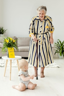 Großmutter im eleganten kleid, das enkelkind betreut