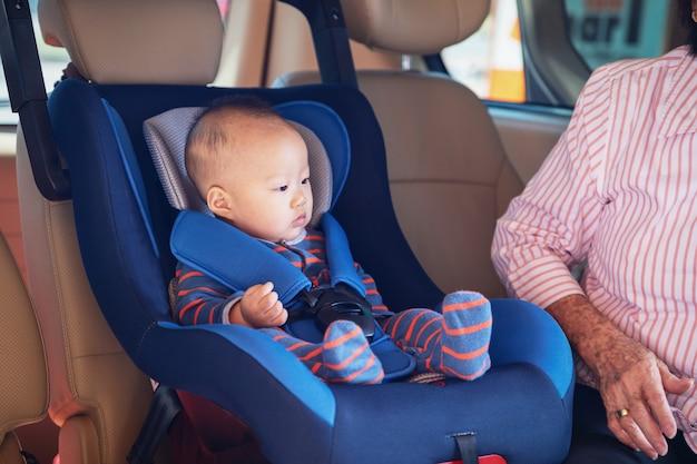 Großmutter kümmert sich um ihre kleine enkelin in einem auto, hilft ihr und jubelt auf