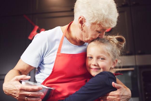 Großmutter küsst und umarmt ihre enkelin