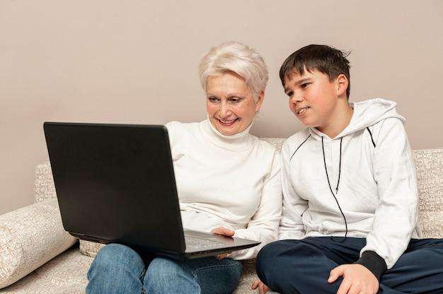Großmutter mit dem enkel, der laptopmodell verwendet