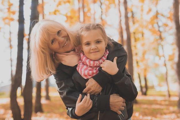Großmutter mit enkelin in herbstparkgeneration und familienkonzept