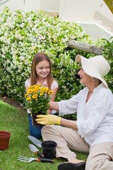 Großmutter mit ihrer enkelin, die im garten arbeitet