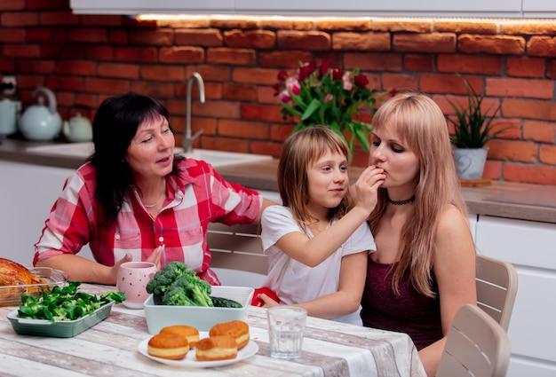 Großmutter, mutter und enkelin nehmen sich zeit in der küche