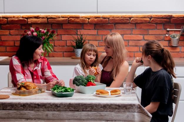 Großmutter, mutter und enkelinnen nehmen sich zeit in der küche