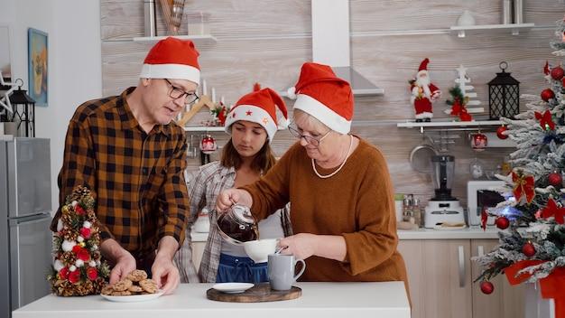 Großmutter setzt kaffee in die tasse und serviert gebackene leckere schokoladenkekse