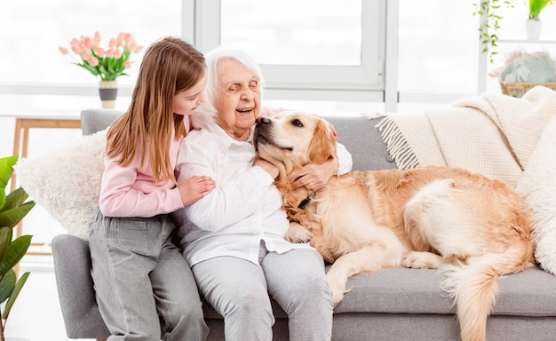 Großmutter sitzt auf dem sofa mit enkelin und golden retriever hund und umarmt sich