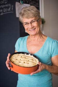 Großmutter stolz auf ihren hausgemachten kuchen