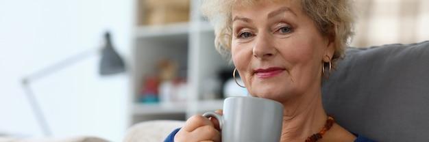 Großmutter trinkt kaffee und liest buch in der wohnung. schöne ältere frau im ruhestand sitzen zu hause auf der couch und ruhen sich aus.